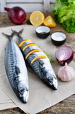 Fresh mackerel fish with a lemon, bow, salt and pepper on a wooden table Stock Photography