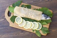Fresh mackerel on paper in grape leaves with lemon. Slices stock image