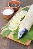 Fresh mackerel on paper in grape leaves. With lemon slices Stock Images