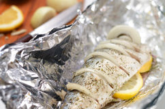 Fresh mackerel prepared for oven cooking, marinated with spices, salt and lemon. Raw fish in foil. Royalty Free Stock Photos