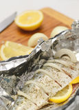 Fresh mackerel prepared for oven cooking, marinated with spices, salt and lemon. Raw fish in foil. Royalty Free Stock Image