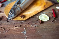 Fresh mackerel on the wooden board with slice of lime and chilli Royalty Free Stock Image