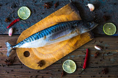 Fresh mackerel on the wooden board with slice of lime and chilli Royalty Free Stock Photography