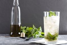 Closeup of fresh mint julep, bottle of alcohol drink and mint as a background.Grey colors mood royalty free stock image