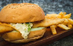 A fresh made Fish Burger on wooden plate close-up shot. A fresh made Fish Burger close-up shot Stock Photo