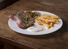Fresh made grilled pork chop steak with french fries chips green stock photos