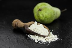 Some healthy Pear powder on a vintage slate slab selective focu. Fresh made Pear powder on a slate slab close-up shot; selective focus stock photography