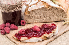 Fresh made Raspberry Jam. On a slice of bread on rustic background Royalty Free Stock Image