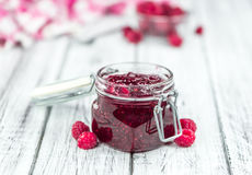 Fresh made Raspberry Jam on a rustic background. Homemade Raspberry Jam on an wooden table as detailed close-up shot; selective focus Royalty Free Stock Photography