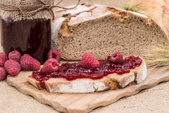 Fresh made Raspberry Jam. On a slice of bread on rustic background Stock Photo