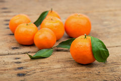 Fresh mandarin oranges fruit with leaves in old wooden table Royalty Free Stock Images