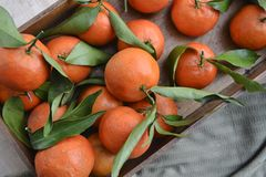 Fresh mandarin oranges fruit or tangerines with leaves on the wooden box on the table. stock photo
