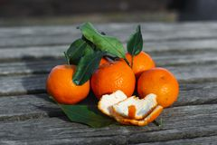 Fresh mandarin oranges fruit or tangerines with leaves on a wooden table stock images