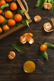 Fresh tangerine oranges on a wooden table. Peeled mandarin. Halves, slices and whole clementines closeup. Fresh mandarin oranges in wooden tray, whole, halved Stock Image