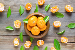 Fresh mandarins in wooden bowl with leafs on old wooden Stock Image