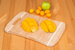 Fresh mango on a cutting board with Fresh Kumquats and a lime, on a wooden table Stock Photos
