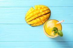 Fresh mango drink and cut fruit on blue wooden table. Top view. Space for text stock photography
