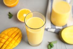 Fresh mango drink and tropical fruits. On table royalty free stock photo