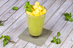 Fresh mango fruit juice in a glass and slices of mango Royalty Free Stock Photos