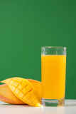 Fresh mango juice. In a glass over green background Royalty Free Stock Photo