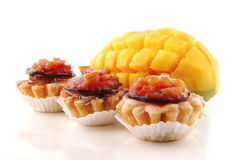 Fresh mango and small cakes. Fresh mango and small fruit cakes served Royalty Free Stock Images