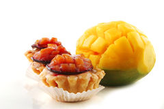 Fresh mango and small cakes. Fresh mango and small fruit cakes served Royalty Free Stock Image