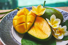 Fresh mango on a wooden tabel with tropical background. Soft focus. Fresh mango in the plate on a wooden tabel with tropical background. Soft focus Stock Photography