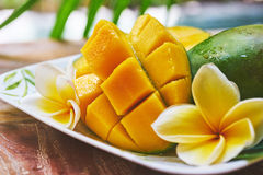 Fresh mango on a wooden tabel with tropical background. Soft focus. Fresh mango in the plate on a wooden tabel with tropical background. Soft focus Royalty Free Stock Photography