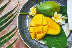 Fresh mango on a wooden tabel with tropical background. Soft focus. Top view of fresh mango in the plate on a wooden tabel with tropical background. Soft focus Royalty Free Stock Images