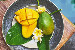 Fresh mango on a wooden tabel with tropical background. Soft focus. Top view of fresh mango in the plate on a wooden tabel with tropical background. Soft focus Stock Image
