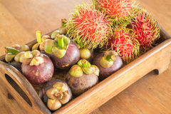 Fresh mangosteen and ranbutan on wooden tray Royalty Free Stock Image