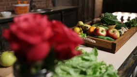 Fresh market fruits and vegetables in wooden tray. Lying on the table in household kitchen. Foreground bouquet of red roses in water-glass. Selective focus stock video