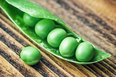 Fresh mature pod of green peas on the old wooden background Royalty Free Stock Photography