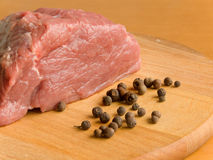 Fresh meat. With black pepper on the wooden board Royalty Free Stock Photo
