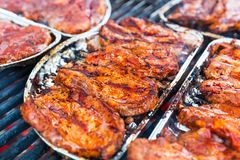 Fresh meat for babecue on grille. Macro view of fresh raw pork marinated meat with spices and seasonings for barbecue Stock Images