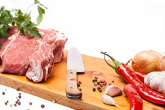Fresh meat of beef with bone on wooden spices and knife Royalty Free Stock Image