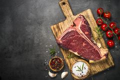 T-bone beef steak on black with spices. stock photos