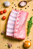 Fresh meat and condiments on cutting board. Fresh raw pork chop meat, chef knife, spices, vegetables and herbs on wooden cutting board background, top view Stock Photo