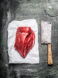 Fresh meat for cooking with meat cleaver large on rustic background. Top view Stock Images