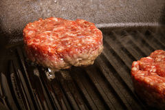 Fresh meat cutlets in a frying pan grill. CloseUp. Toned Stock Images