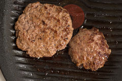 Fresh meat cutlets in a frying pan grill Royalty Free Stock Images