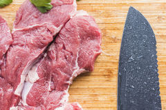 Fresh meat and a cutting knife. Fresh juicy red meat and a large black cutting knife lying on a light brown wooden kitchen board.Beautiful and healthy cooking Stock Photos