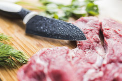 Fresh meat, dill, parsley and a knife. Fresh red beef meat, bright green dill and parsley, a knife with a black wide blade on a light bamboo board. Beautiful and Royalty Free Stock Photos