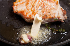 Fresh meat is fried in a frying pan with thyme and garlic. Selec Royalty Free Stock Image