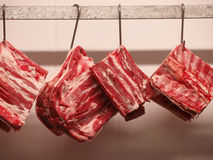 Fresh meat hanging on hooks Royalty Free Stock Images