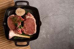 Fresh meat with ingredients for cooking in a pan on dark table, top view royalty free stock photos