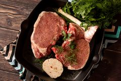 Fresh meat with ingredients for cooking in a pan on dark table, top view stock photo