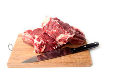 Fresh meat with knife. On a kitchen board Stock Photos
