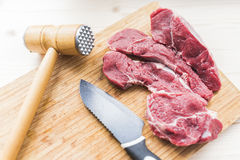 Fresh meat, knife and hammer for beating meat. Fresh bright red beef meat, a black knife with a wide blade and a wooden hammer to beat the meat on a light bamboo Stock Image