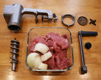 Fresh meat with onions become meat grinder. Stock Photos